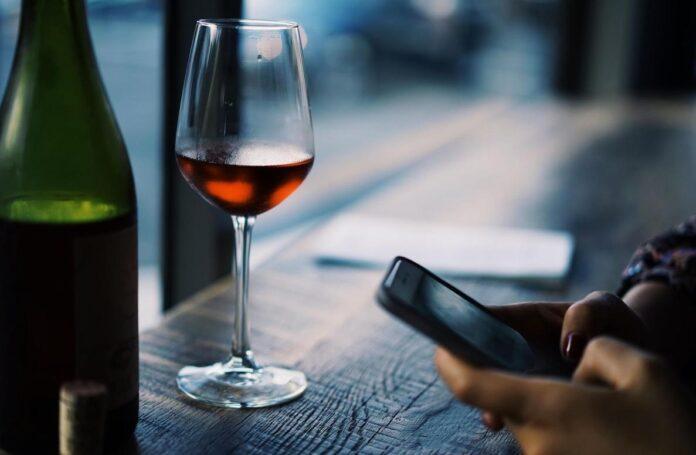 Homme avec son téléphone et un verre de vin