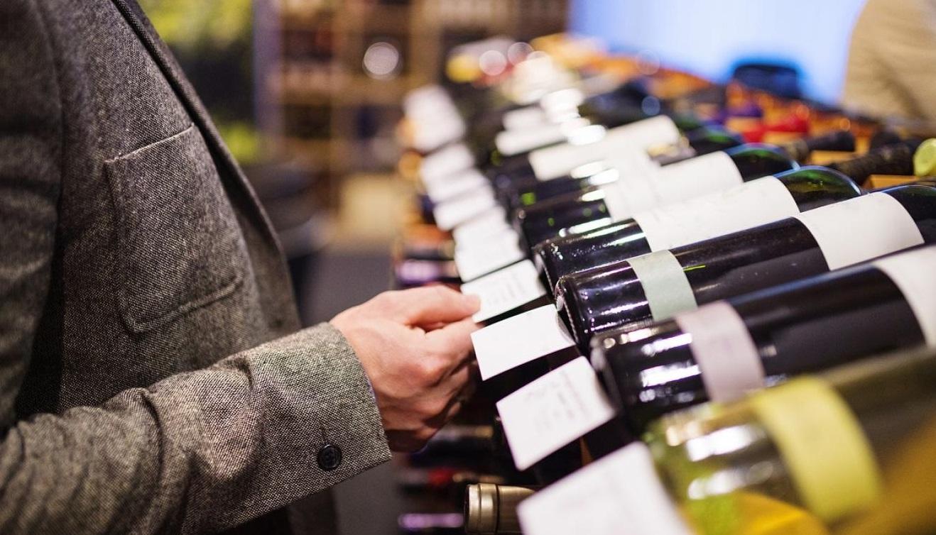 Personne qui cherche une bouteille de vin