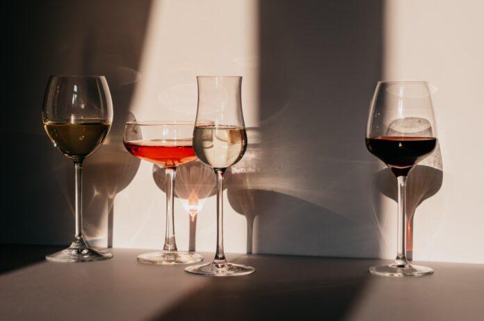 quatre verres de vin blanc rouge rosé contre mur blanc
